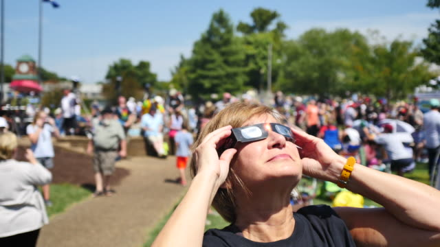 eclipse watchers view the sun with eclipse glasses at little river park as the moon begins to block the sun during the total solar eclipse august 21... - solar eclipse glasses stock videos and b-roll footage