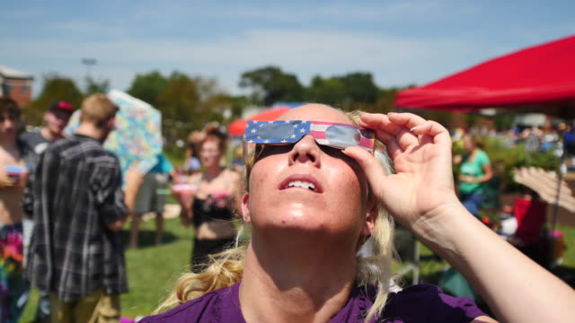 Eclipse watchers view the sun with eclipse glasses at Little River Park as the moon begins to block the sun during the total solar eclipse August 21...