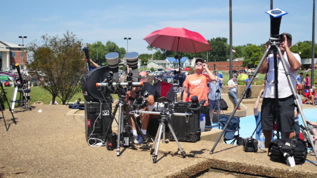 stockvideo's en b-roll-footage met professional and amateur photographers and eclipse watchers line an area at little river park as the moon begins to block the sun during the total... - de ruimte en astronomie