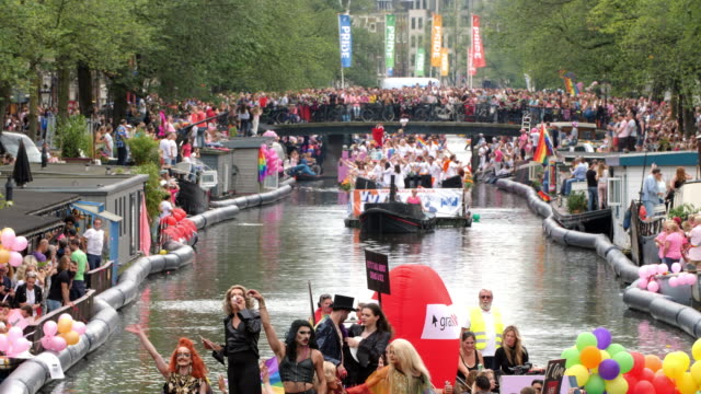 horizontal color footage of people celebrating the annual canal parade of amsterdam pride in 2017 - dutch culture stock videos & royalty-free footage