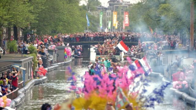 Horizontal color footage of people celebrating the annual canal parade of Amsterdam Pride in 2017