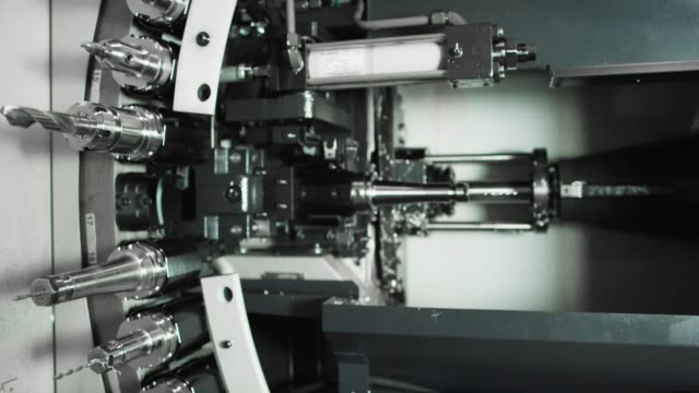 a horizontal machining center changes out a drill bit as other tools rotate in a tool changer machine in a manufacturing facility - cut video transition video stock e b–roll