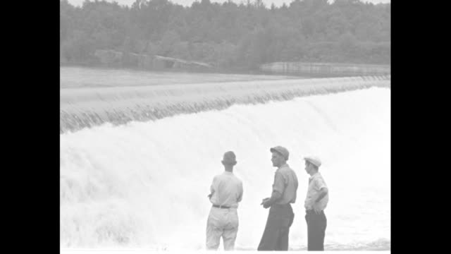 vídeos de stock e filmes b-roll de horizontal pan of water coming over ashokan dam in catskill park in the catskill mountains / ms three men watch water coming over dam / vs water... - appalachia