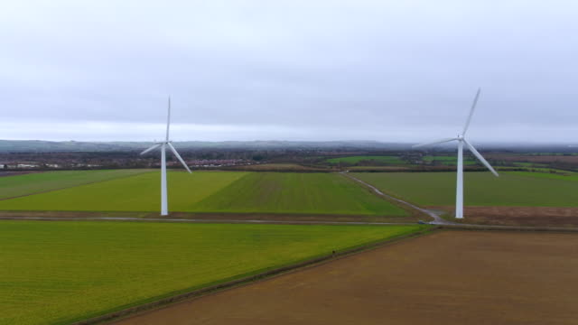 vídeos de stock, filmes e b-roll de horizontal tracking shot to reveal row of wind turbines - energy efficient