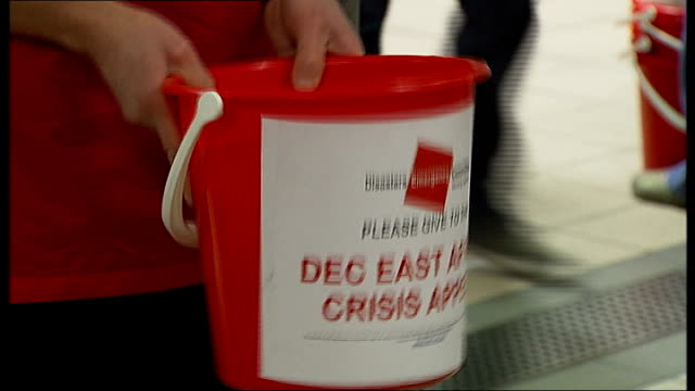 un calls emergency meeting england london euston station int various shots london underground workers with buckets collecting donations for the dec... - horn of africa stock videos & royalty-free footage