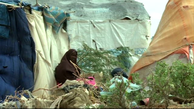 un calls emergency meeting woman sits amongs makeshift tents - horn of africa stock videos & royalty-free footage