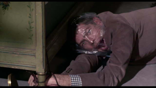 1963 Horrified woman (Audrey Hepburn) discovers chained and suffocated body of man (James Coburn)