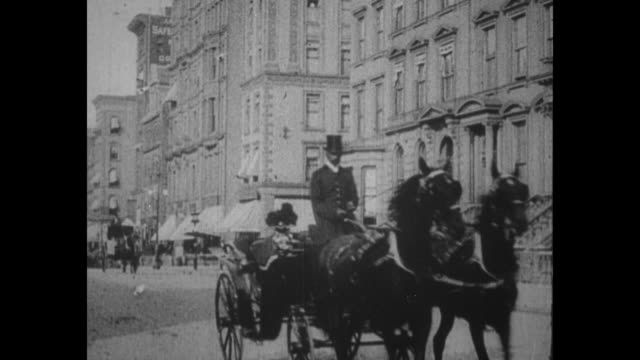 horse and carriage approach as they move on streets of city / police officer in bobbytype helmet directs traffic as trolleys move on street trolley... - cocchio video stock e b–roll