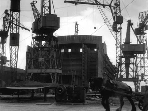 a horse and cart moves past a ship under construction at the port glasgow shipyard - zugpferd stock-videos und b-roll-filmmaterial