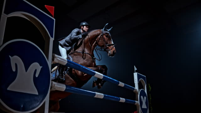 SLO MO A horse and his rider jumping a rail in the arena