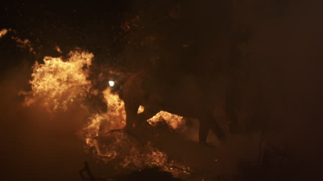F/S horse and riders crossing a big bonfire and struggling against big flames, smoke