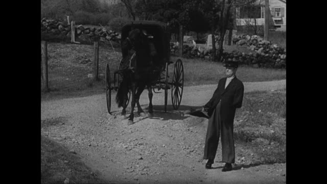horse at crossing, train passing fg. dramatization: old woman waiting at train station. railroad tracks. two men waiting at station checking pocket... - eisenbahnwaggon stock-videos und b-roll-filmmaterial
