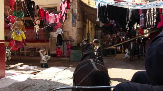 vídeos de stock, filmes e b-roll de ms pov horse carriage moving through bazaar and past man shoveling as well as women in traditional arab clothing / luxor, egypt - áfrica do norte