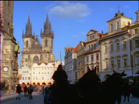 horse + carriage riding past camera in old town square / tyn church in background / prague, czech republic - altstädter ring stock-videos und b-roll-filmmaterial