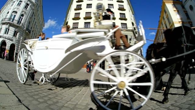 stockvideo's en b-roll-footage met horse drawn carriage and tourists on michaelerplatz, vienna, vienna, austria, europe - koets