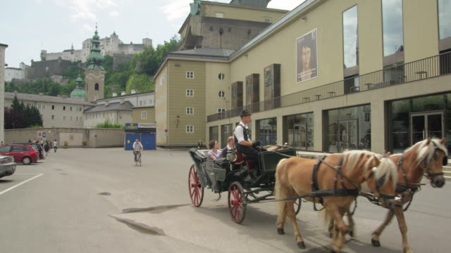 ws horse drawn carriage in front of main entrance to the festspielhaus (festival hall), hohensalzburg castle in background - two animals stock videos and b-roll footage