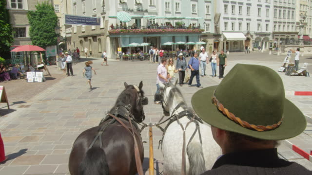 POV WS horse drawn carriage moving through the historic center of Salzburg, crossing the Alter Markt (Old Market) square