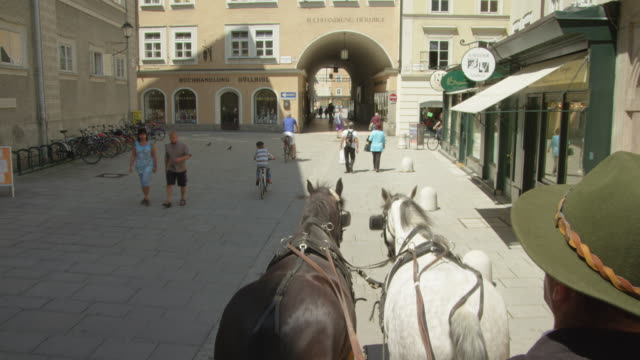 POV WS horse drawn carriage moving through the historic center of Salzburg