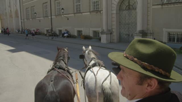 pov ws horse drawn carriage moving through the historic center of salzburg - 馬車点の映像素材/bロール