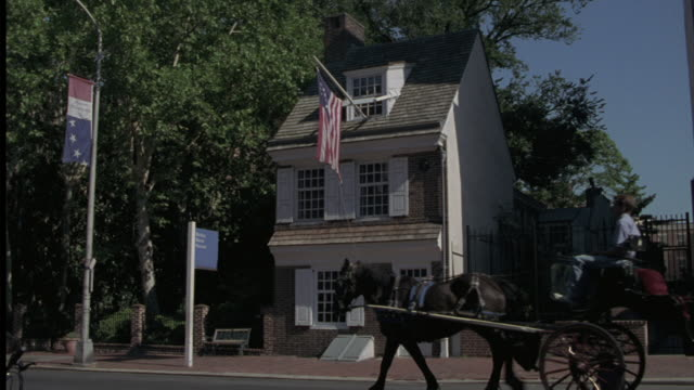 "a horse drawn carriage passes the ""betsy ross house"" in philadelphia. - betsy ross house video stock e b–roll"