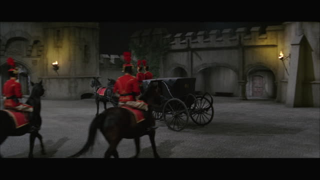 vidéos et rushes de ms pan horse drawn carriage with coachmen on horseback going though castle gate - voiture attelée