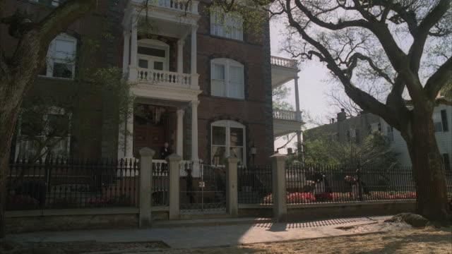 vídeos de stock, filmes e b-roll de ms, reenactment horse drawn carriages and people passing three story brick mansion, 19th century style - estilo século dezenove