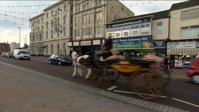 Horse drawn cart travels past Blackpool Pier North Pier entrance