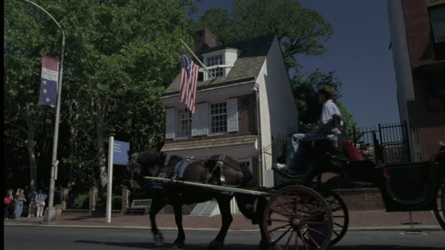 a horse drawn wagon rolls down the street in front of the betsy ross house in philadelphia. - betsy ross house video stock e b–roll