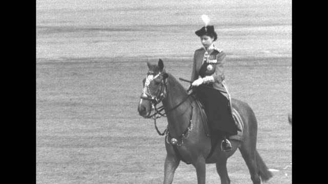 horse guards parade ground/ princess elizabeth sidesaddle on horse back/ princess elizabeth and horse guards ride past guards and spectator stands/... - 軍旗分列行進式点の映像素材/bロール