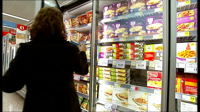 investigations continue london woman taking frozen ready meal out of supermarket freezer and puts it into trolley - cibi surgelati video stock e b–roll