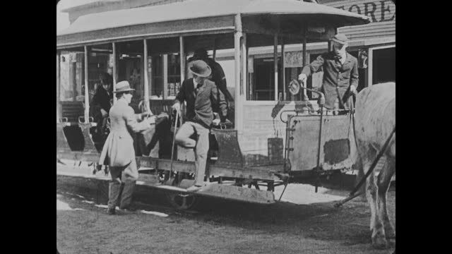 vidéos et rushes de 1918 a horse powered trolley stops in front of a drugstore and a group of men and women begin to step off - 1918