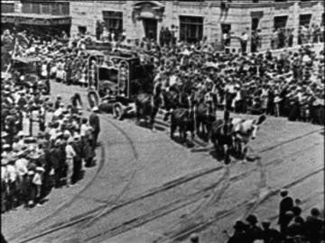 stockvideo's en b-roll-footage met b/w 1928 horse pulling circus wagon as crowd watches on city street / documentary - 1928