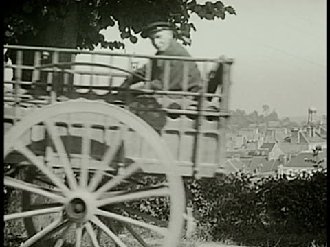 vídeos de stock e filmes b-roll de horse pulling wooden carriage w/ man roofs of houses bg ws farmers w/ cattle carriage in field ws french countryside hills farms ms cannons/casemates... - linha maginot