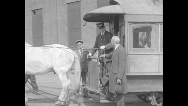 vidéos et rushes de horse pulls old brooklyn city railroad company horse-drawn streetcar out of car barn / henry ford walks past stopped streetcar / ford standing beside... - voiture hippomobile