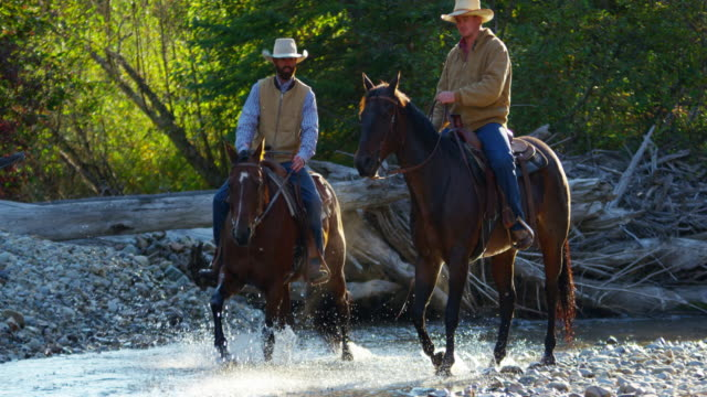 Horse riders in valley stream Rocky mountains USA
