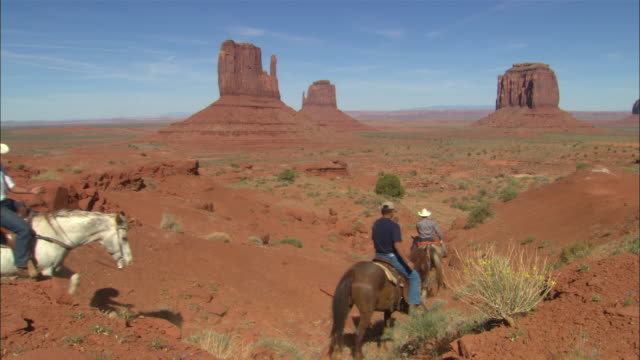Horse riders ride down slope towards 'Mitten' butte formations in Monument Valley Available in HD.