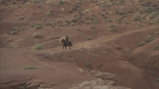 AERIAL POV Horse riding through monument valley / Unspecified