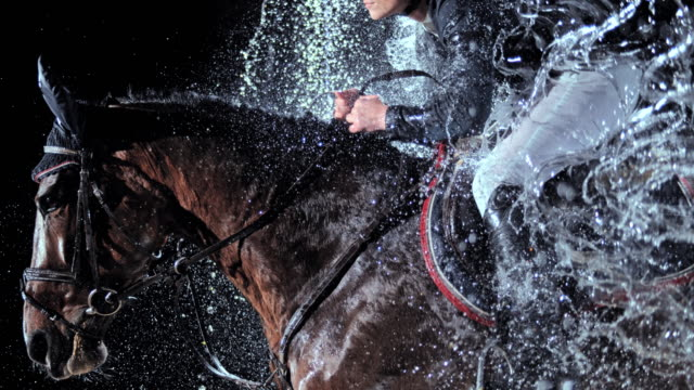 SLO MO Horse with his rider jumping through a waterfall