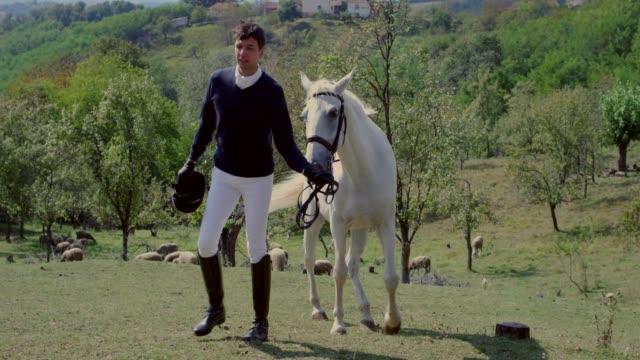 stockvideo's en b-roll-footage met ruiter in de kleding van toonaangevende witte paard door de teugels - alleen één mid volwassen man