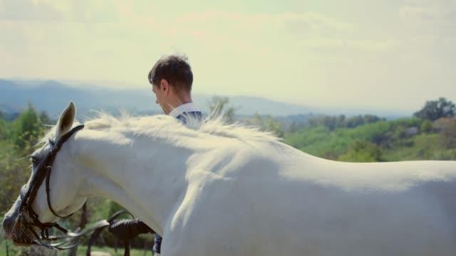 stockvideo's en b-roll-footage met ruiter leiden witte paard door de teugels - alleen één mid volwassen man