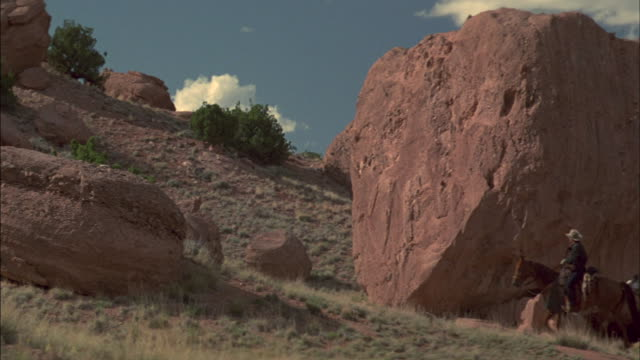 Horseback riders pass by large boulders on the side of a hill.