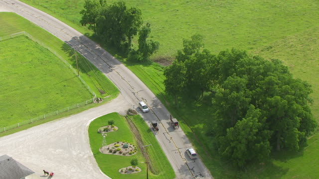 vídeos de stock e filmes b-roll de ws aerial pov horsedrawn carriage and cars moving on road / elkhart county, indiana, united states - amish