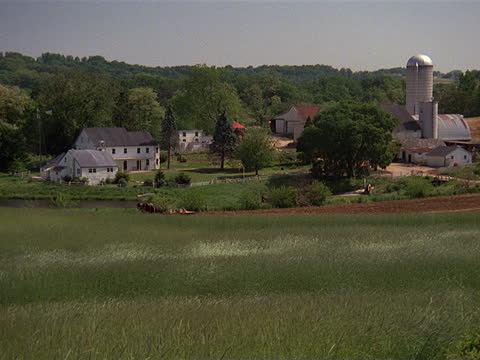 a horse-drawn carriage drives into a farm field in amish country. - amische stock-videos und b-roll-filmmaterial