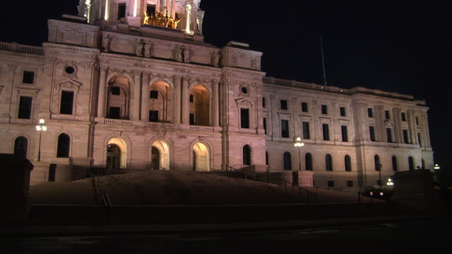 a horse-drawn carriage walks by, silhouetted by the glow of the minnesota state capitol building - saint paul stock-videos und b-roll-filmmaterial