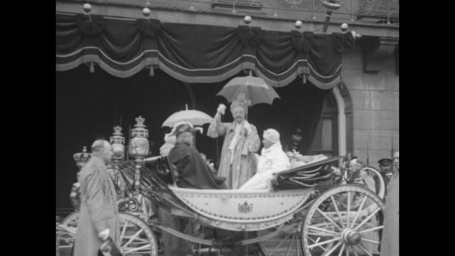 a horsedrawn carriage with queen mother emma of waldeck and pyrmont and queen wilhelmina are escorted by liveried footmen on a rainslicked street /... - フットマン点の映像素材/bロール