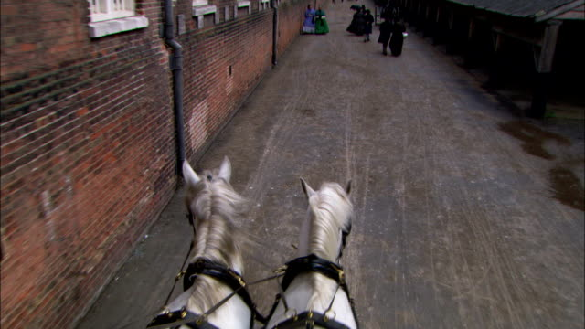 horse-drawn carriages move along a street in london during the 19th century cholera epidemic. - 19世紀点の映像素材/bロール