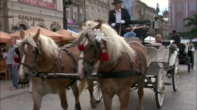 stockvideo's en b-roll-footage met horsedrawn carriages passing camera in front of sidewalk cafes in rynek glowny / old town, krakow, poland - winkelbord