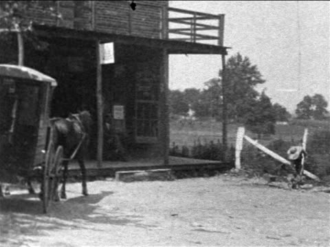 b/w 1903 horsedrawn mail truck pulling up to rural post office / westminster, maryland / newsreel - 1903 stock-videos und b-roll-filmmaterial