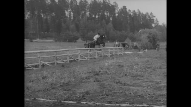 horseman clears water jump at winter olympics equestrian jumping event / horseman jumps fence / another horseman jumps fence crosses road jumps... - 1956 bildbanksvideor och videomaterial från bakom kulisserna