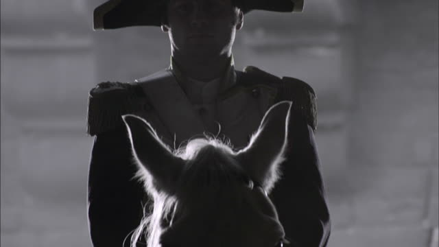 vidéos et rushes de a horseman holds the horse of a uniformed officer in french revolution era clothing. - révolution française